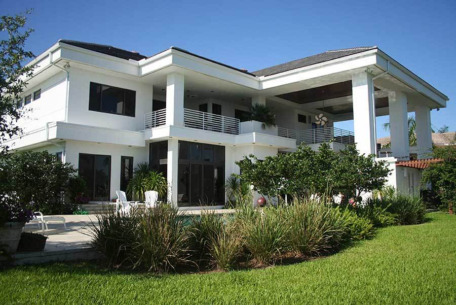 The rear exterior view shows the expansive upper balcony and glass sliding doors that open to the lanai.