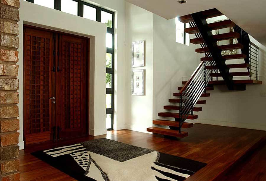 The foyer has a single stringer staircase, a large area rug, and a wooden double entry door that blends in with the rich hardwood flooring.