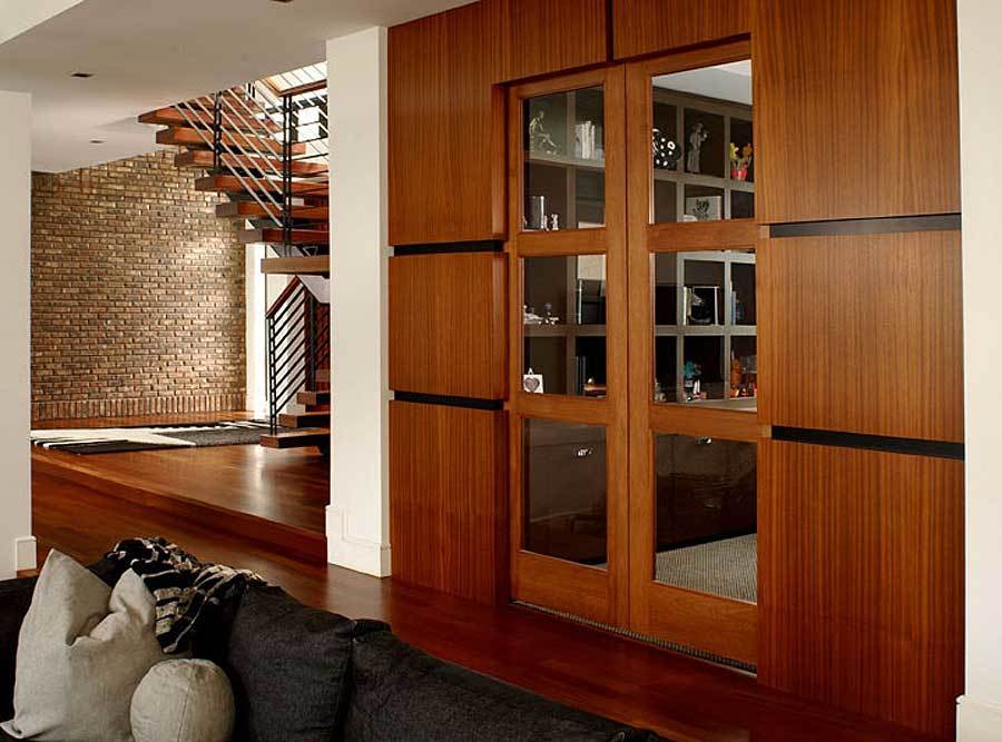 A modern french door behind the comfy sofa leading to the study.