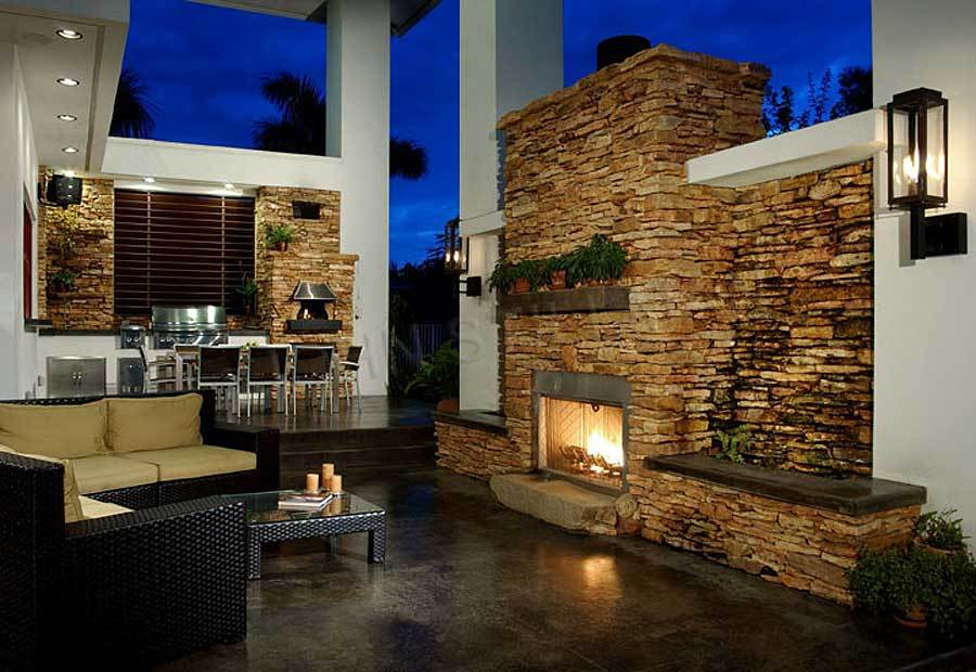 Rear patio containing a summer kitchen, outdoor dining, and living warmed by a brick fireplace.