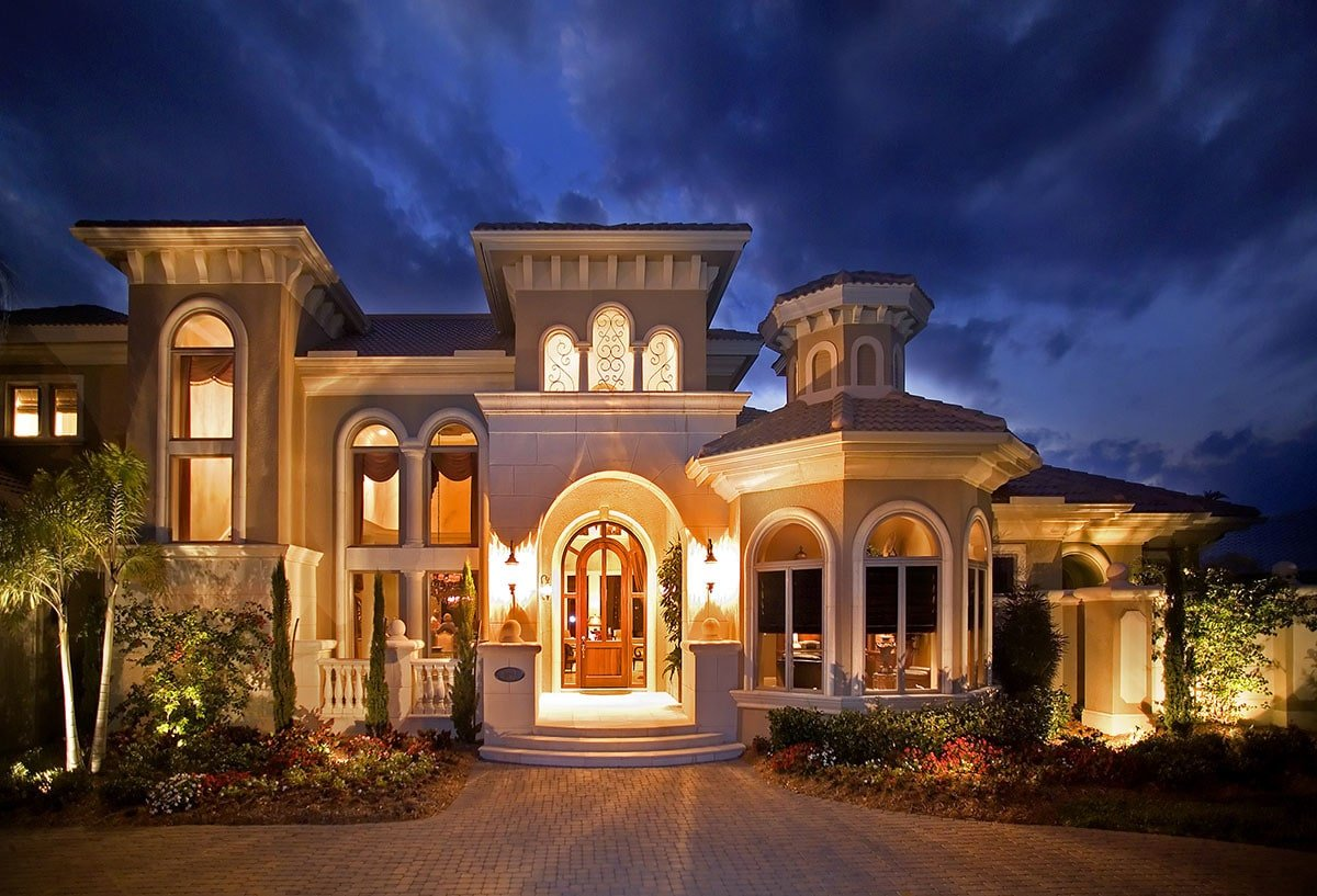 Home's entry showcasing an arched front door flooded by the warm lights of the interior and exterior.