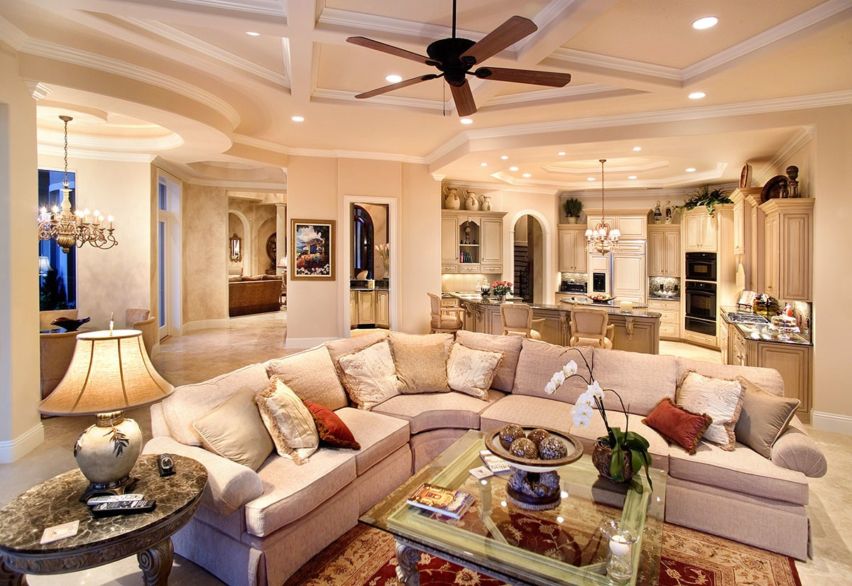 The family room offers an L-shaped sectional, a glass top coffee table, and a fan mounted on the tray coffered ceiling.