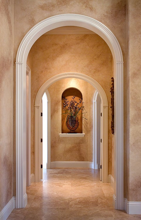 An arched hallway with marble walls and an arched inset filled with lovely decor.