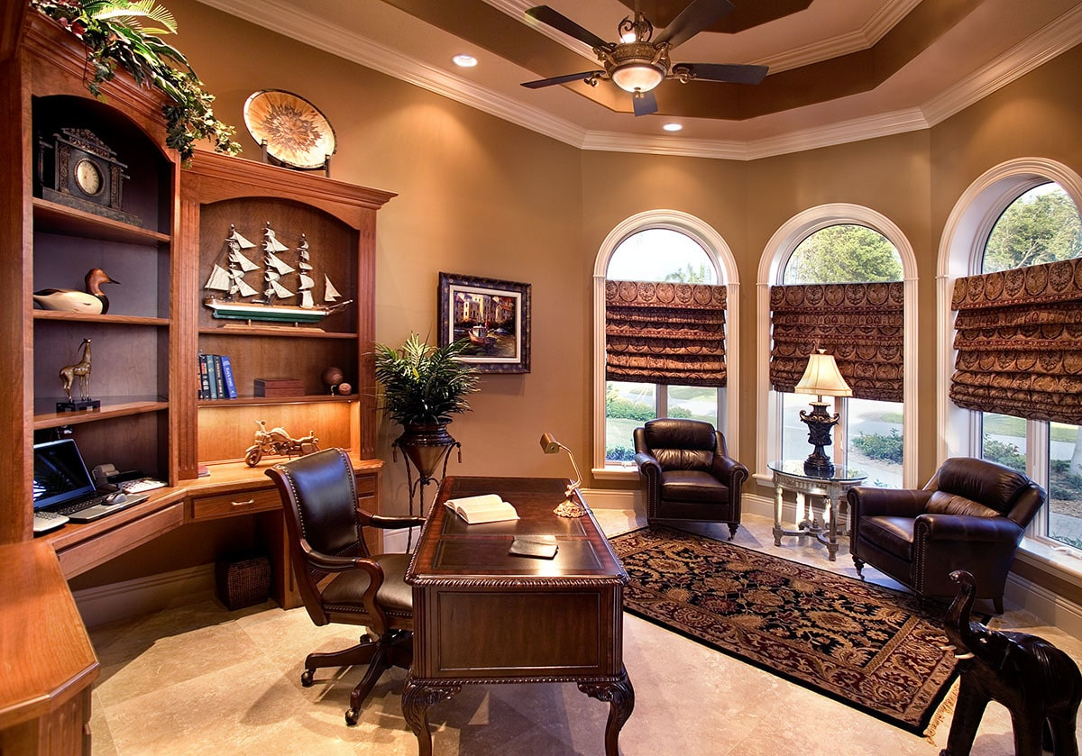 The study has wooden furnishings, a stunning tray ceiling, and arched windows dressed in patterned shades.