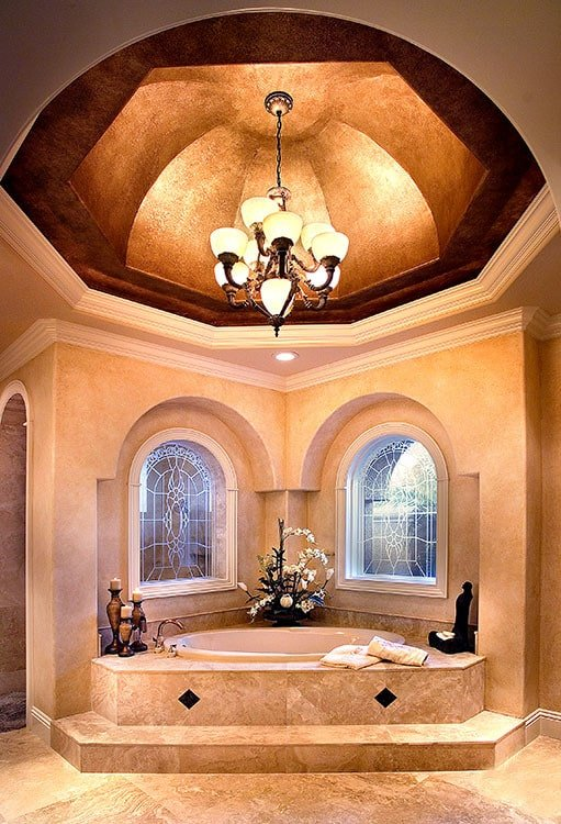 An opulent primary tub situated under the stunning dome ceiling mounted with a warm chandelier.