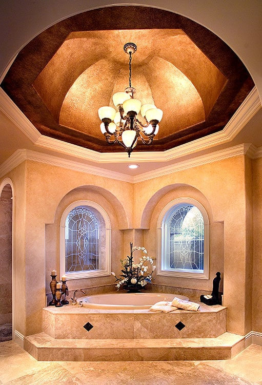 An opulent master tub situated under the stunning dome ceiling mounted with a warm chandelier.