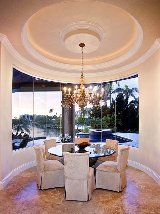 A closer look at the breakfast nook shows the panoramic window overlooking the sparkling pool.