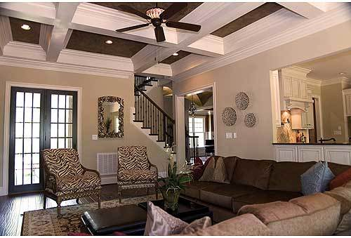The living room has a coffered ceiling and a french door that leads out to the rear porch.