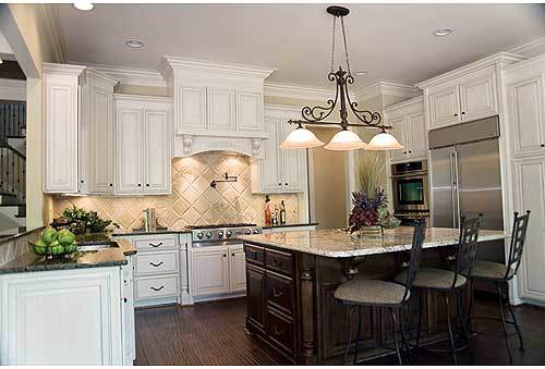 A large breakfast island bar illuminated with warm dome pendants complete the kitchen.