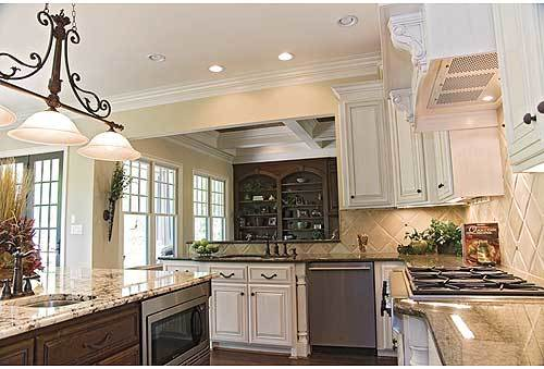 The kitchen is equipped with stainless steel appliances, undermount sinks, and elegant granite countertops.