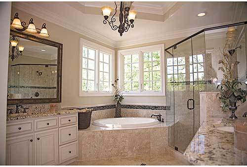 The primary bathroom boasts a deep soaking corner tub flanked with white vanity and a walk-in shower enclosed in glass.