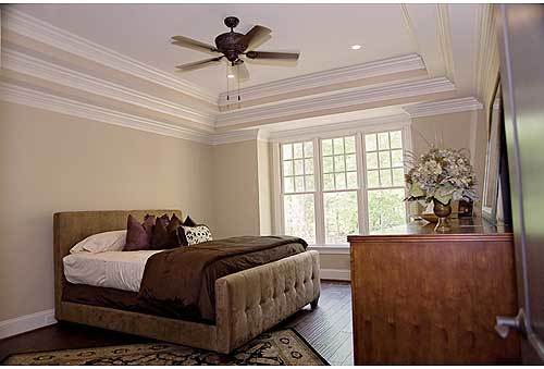 Primary bedroom with a wooden dresser, beige tufted bed, and a classic area rug that lays on the hardwood flooring.