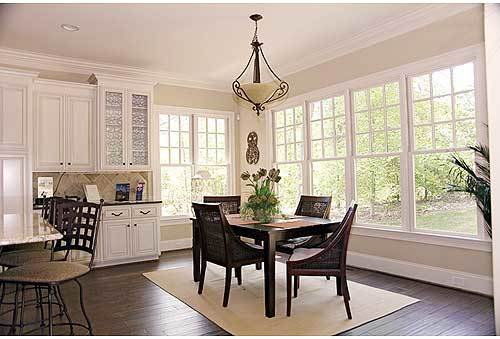Breakfast nook with an ornate pendant light and a dark wood dining set sitting on a beige area rug.