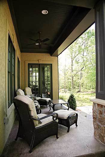 The porch is filled with cushioned wicker seats and a dark wood table that matches the wood-paneled ceiling.