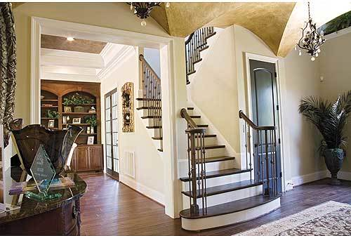 The foyer offers a traditional staircase and wrought iron chandeliers that hang from the groin vault ceiling.