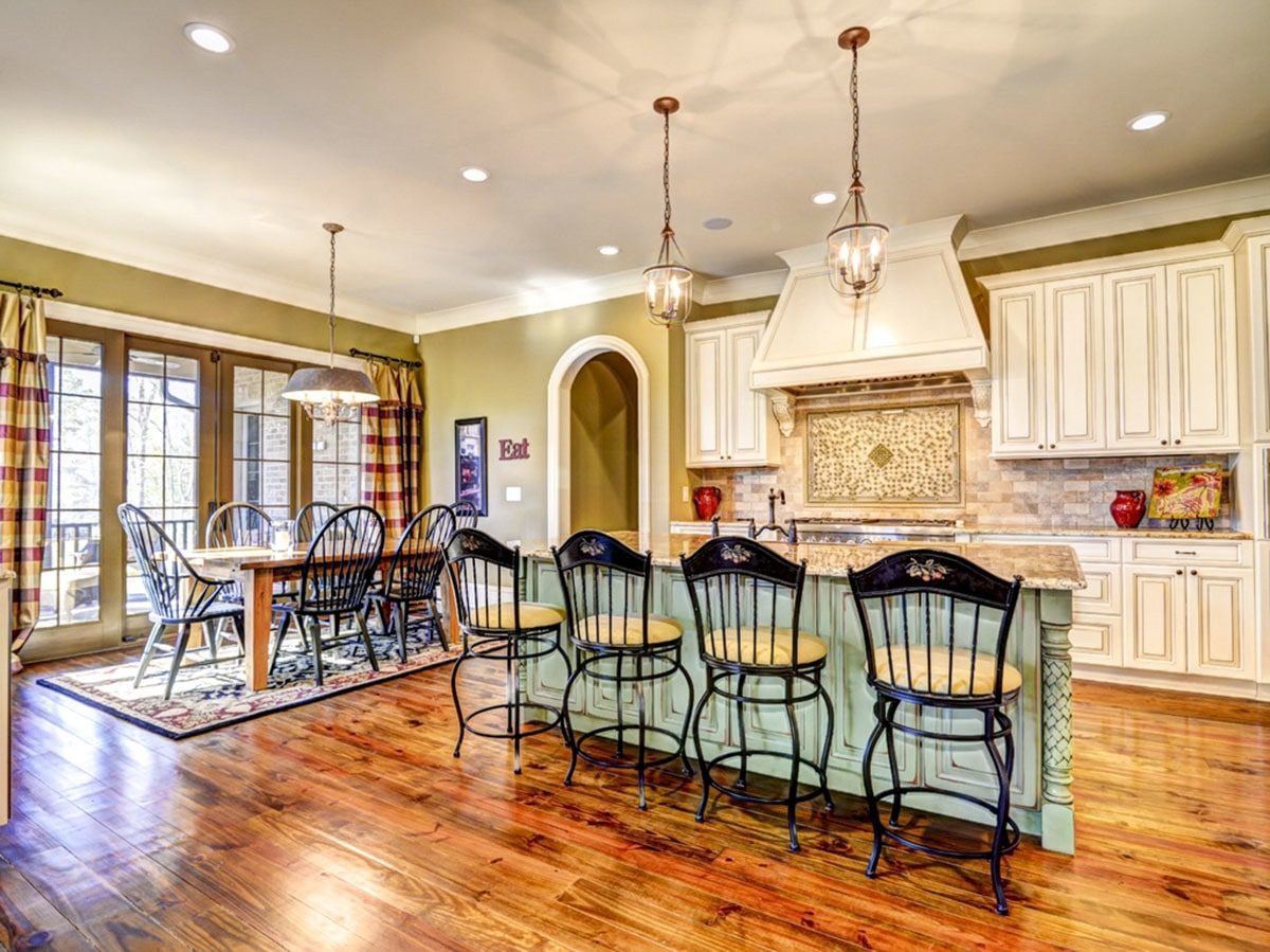 Across the kitchen is the dining area offering metal round back chairs and a wooden dining table sitting on a classic area rug.