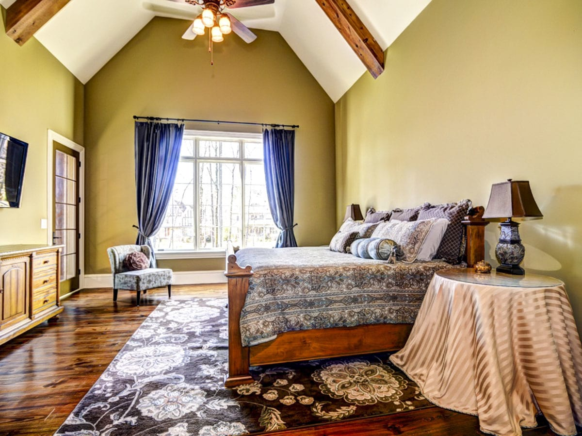 The primary bedroom has rich hardwood flooring, moss green walls, and a high vaulted ceiling lined with natural wood beams.