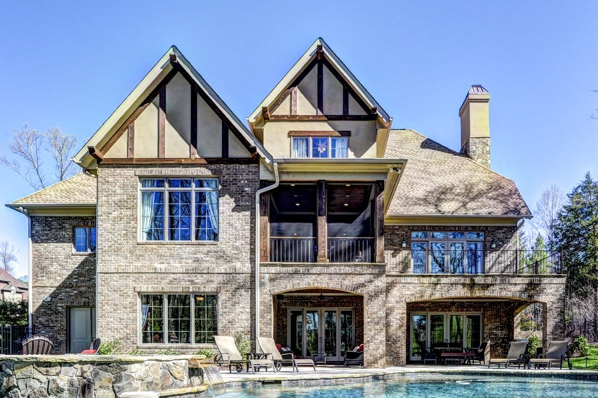 View of the Tudor home from the background showing the stone brick exterior, covered lanais, and a sparkling pool integrated with a relaxing spa.