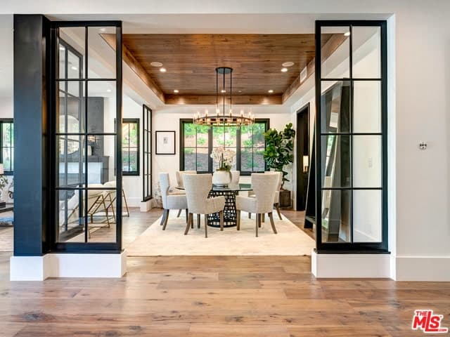 This is a formal dining room adorned with glass panels accented by the black frames. These match with the frames of the large leaning mirror and the legs of the round glass-top dining table topped with a black wrought-iron chandelier.