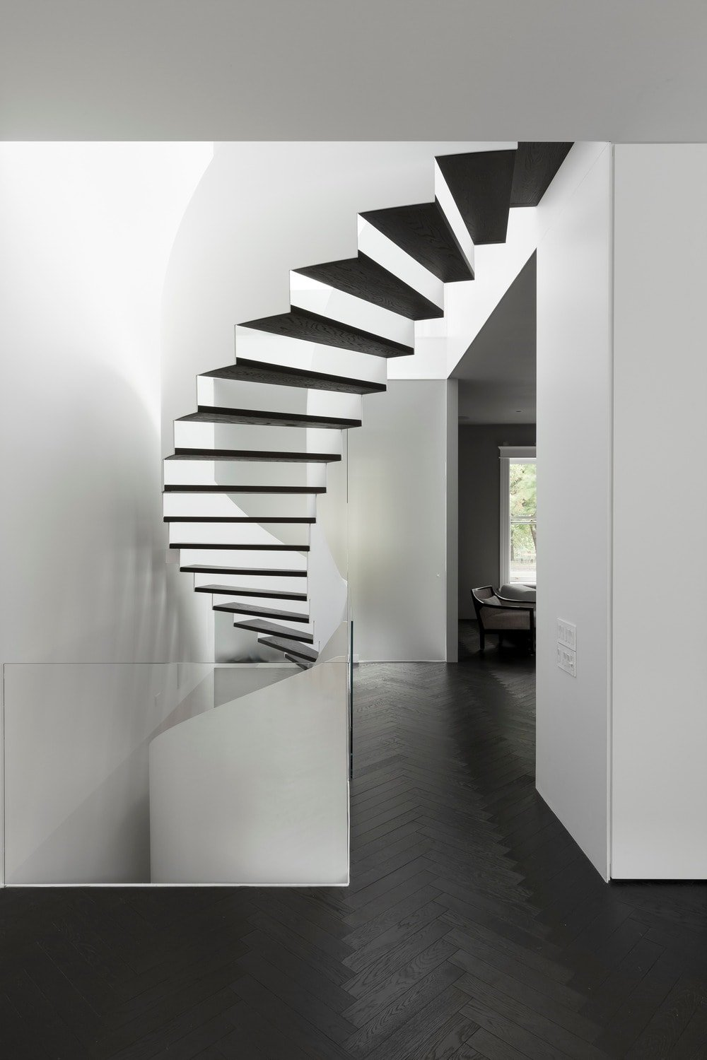 This is the view of the black and white modern spiral staircase from the vantage of the second floor landing. Its design gives it an almost artistic monochromatic look.