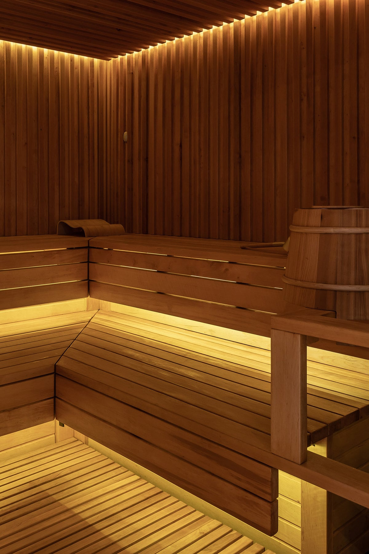 There is also a steam room with built-in wooden benches that blend perfectly with the wooden walls and flooring. This built-in bench has a lovely design on its lighting making it glow at the edges to help when the room is filled with steam.