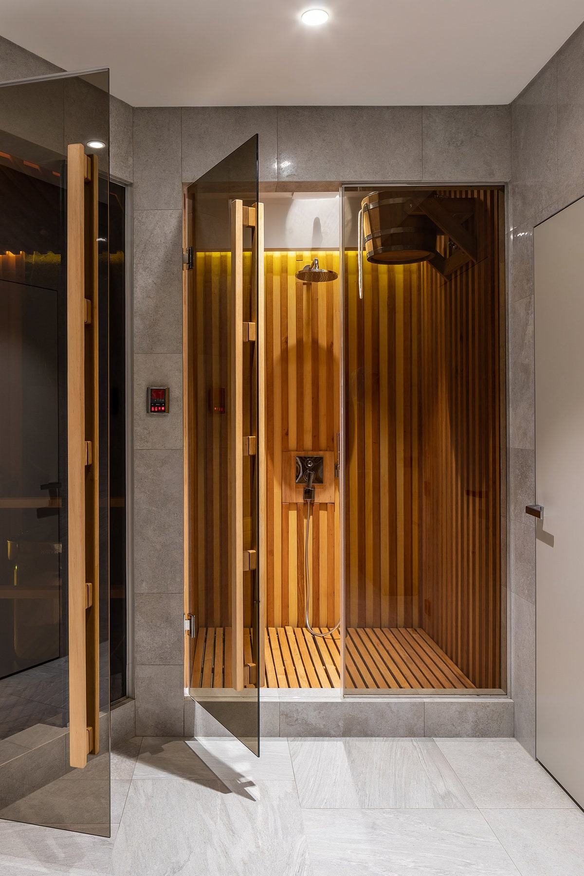 This house also has a shower area near the pool. This has lovely glass doors and wooden sauna-type walls inside to match its flooring.