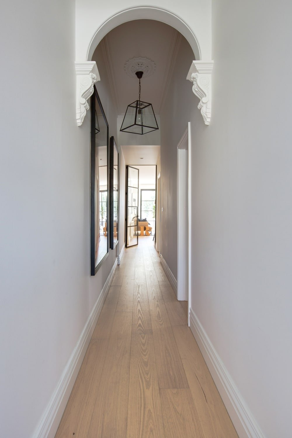 This is a simple hallway-like foyer with white walls, a white arch and a light hardwood flooring to be contrasted by the black lantern-like pendant light and the frames of the wall-mounted artworks.