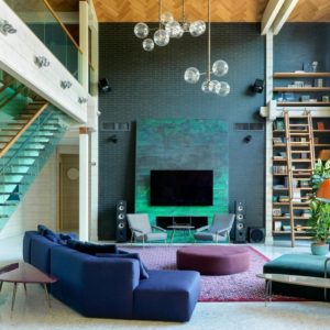 This is the lovely and colorful living room with a tall ceiling that hangs a set of decorative lighting. The highlight of this living room is the large green wall with a green panel that houses the modern fireplace and the TV.