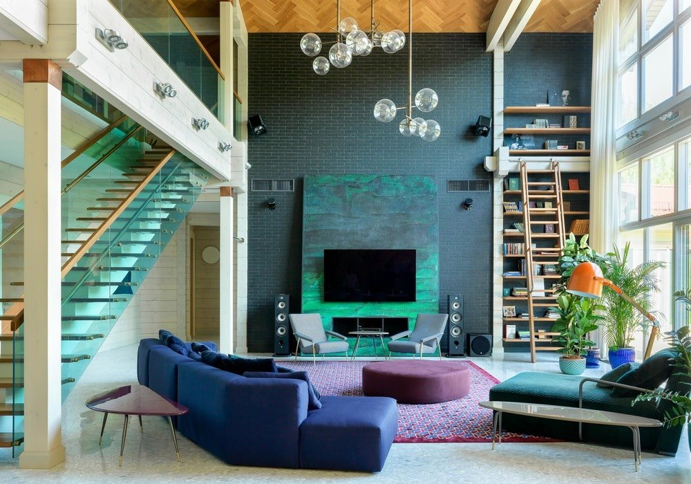 This is the beautiful and colorful living room with a tall ceiling that hangs a set of decorative lighting. The highlight of this is the lovely green wall with a green panel that houses the modern fireplace and the TV.