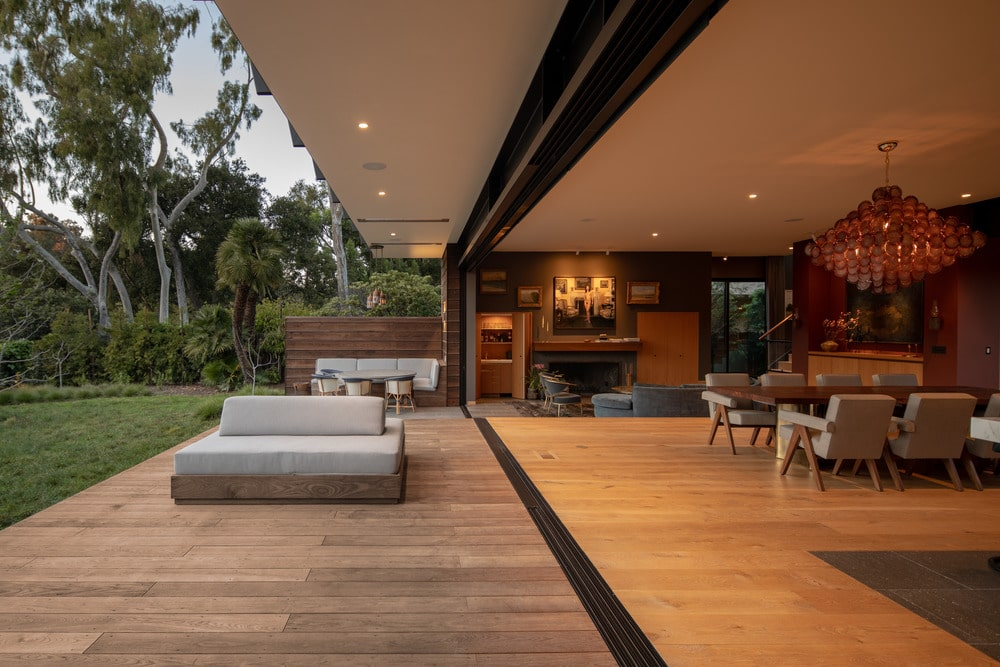 This is the other open wall of the dining area with a wooden deck patio that has an outdoor sofa and an outdoor dining area on the far side against a wooden wall.