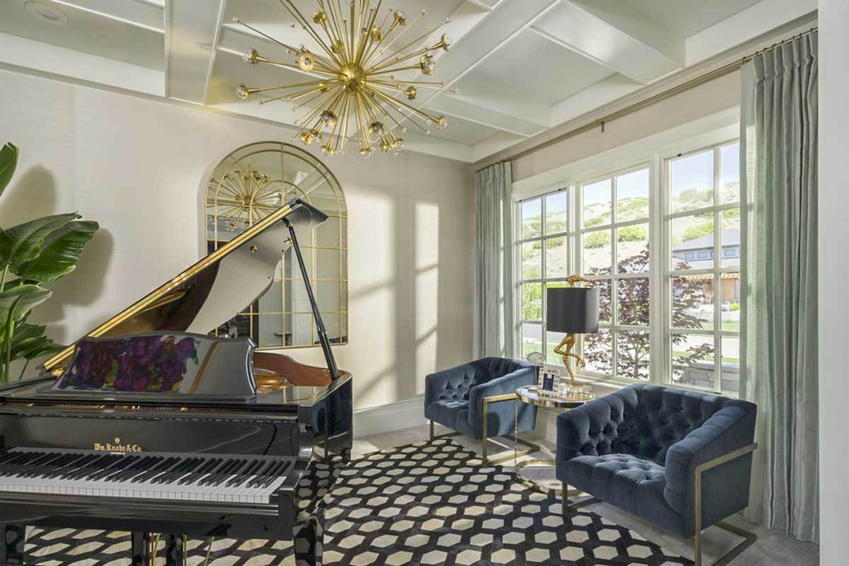 Living room with a baby grand piano, blue tufted armchairs, and a sputnik chandelier that hangs from the coffered ceiling.