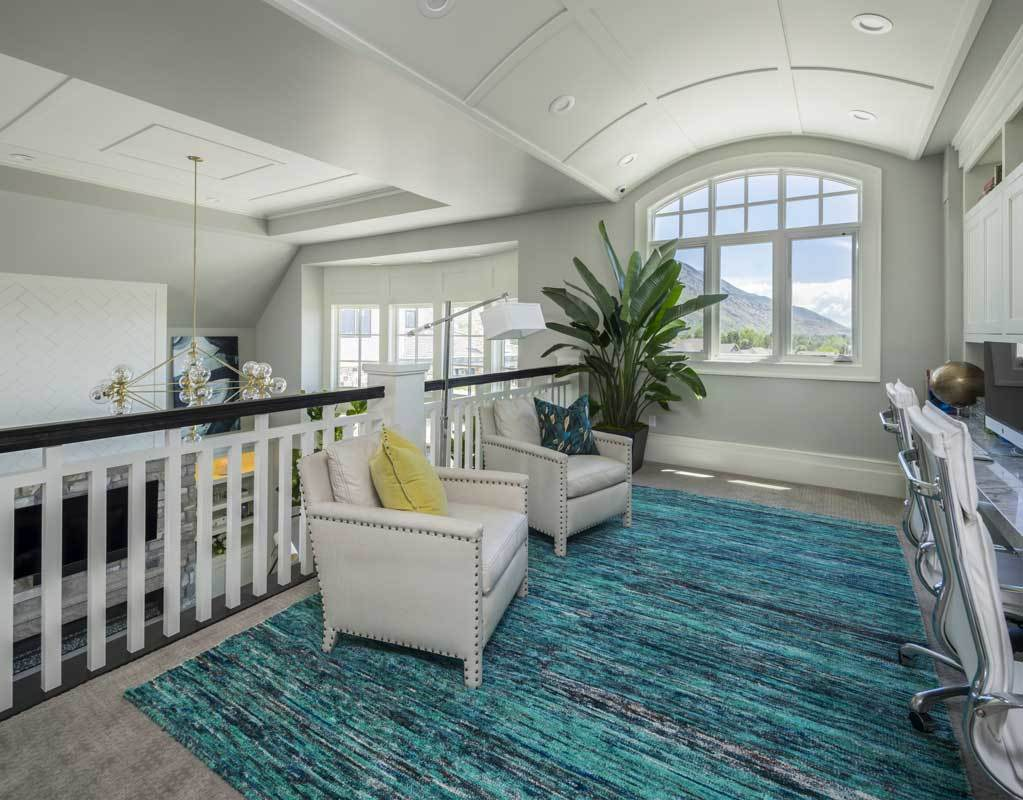Second-floor loft with a barrel vaulted ceiling and gray carpet flooring topped with a large bold area rug.