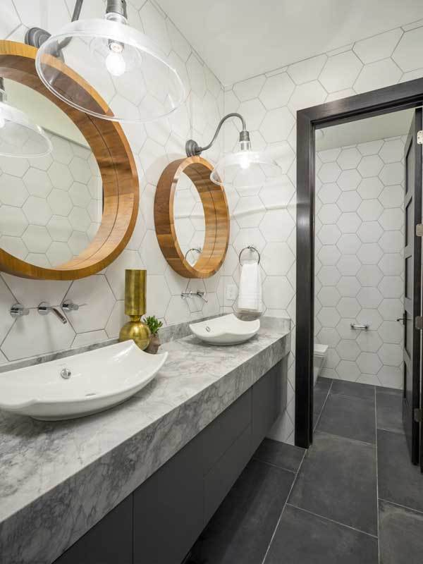 This bathroom offers a toilet room and dual vanities with stylish vessel sinks under the round statement mirrors and oversized glass dome sconces.