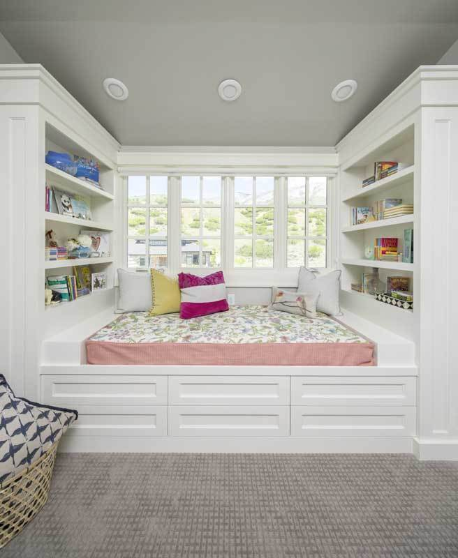 A reading nook by the white framed window with built-in shelves flanking the cushioned sit topped with cute pillows.