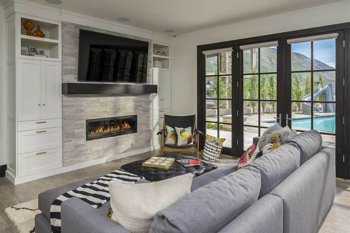 The recreation room has a gray sectional sofa, modern fireplace under the wall-mounted TV, and a french door that leads out to the lanai and pool.