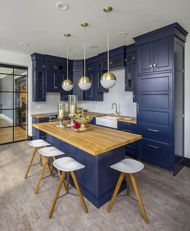 A closer view of the snack bar with deep blue cabinets and an island complemented with brass globe pendants and sleek bar stools.