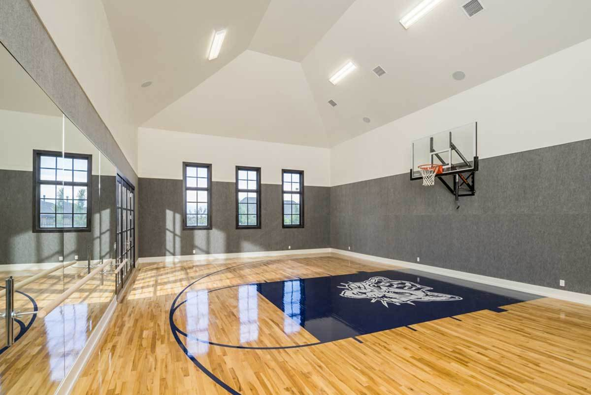 Sports court with vaulted ceiling, polished hardwood flooring, and dual tone walls mounted with a basketball ring.