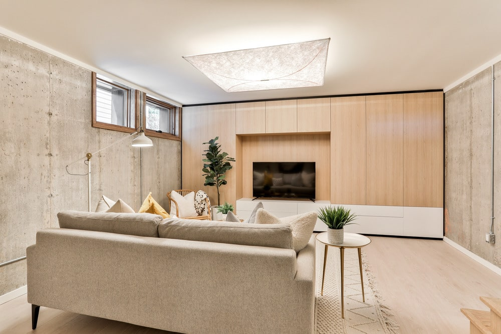 This is a lovely basement fitted with a gorgeous living room. It has a beige sofa that pairs quite well with the wooden wall panel across from it that houses a modern fireplace adorned with a potted plant on the side.