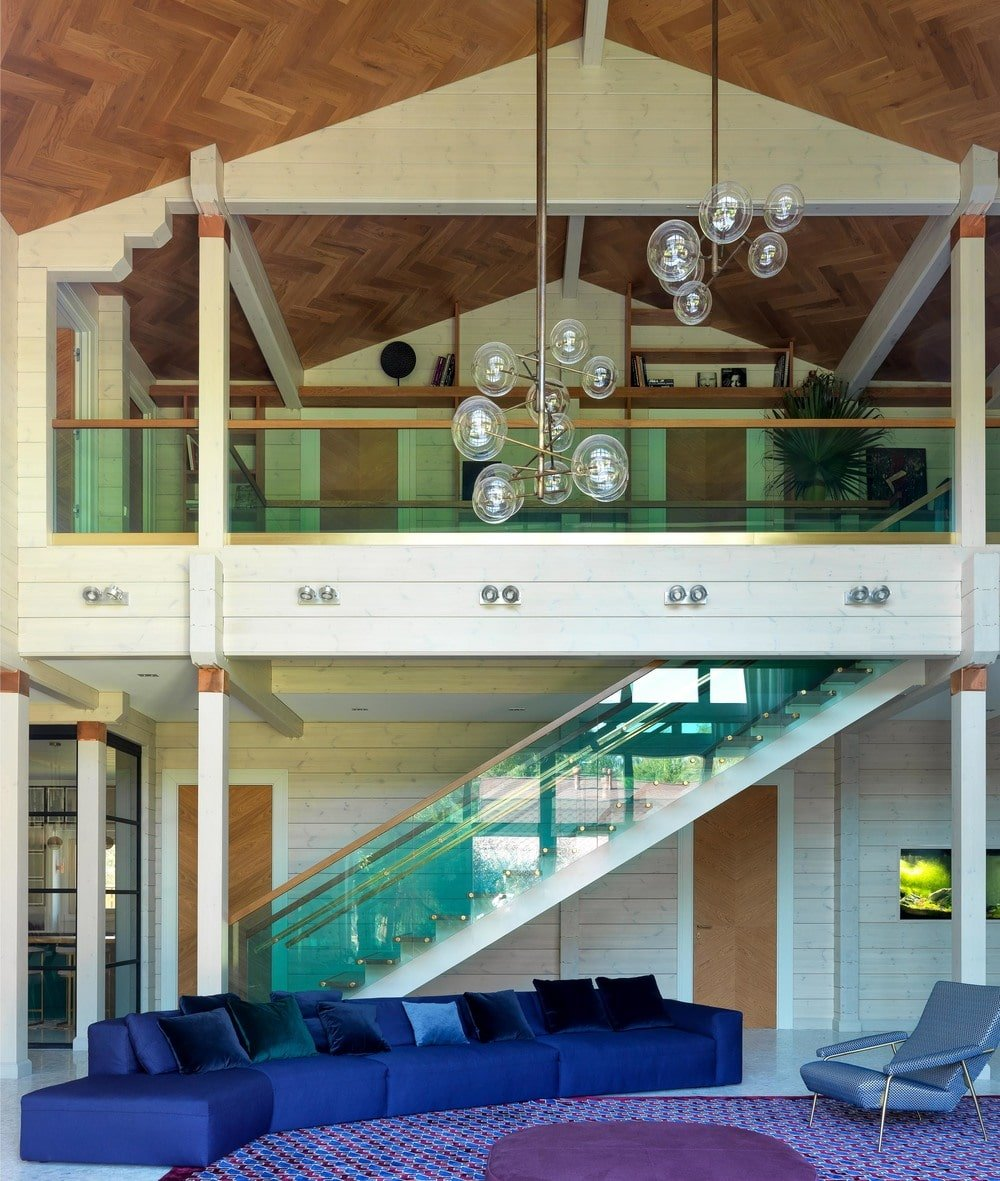 This view of the living room focuses on the large blue velvet sectional sofa beside the staircase with glass sides matching those of the indoor balcony above.