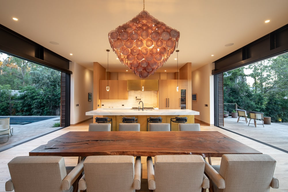 This is a close look at the dining area of the great room. Here you can see that the large dining table has a darker wooden tone as the light hardwood flooring and the ceiling.