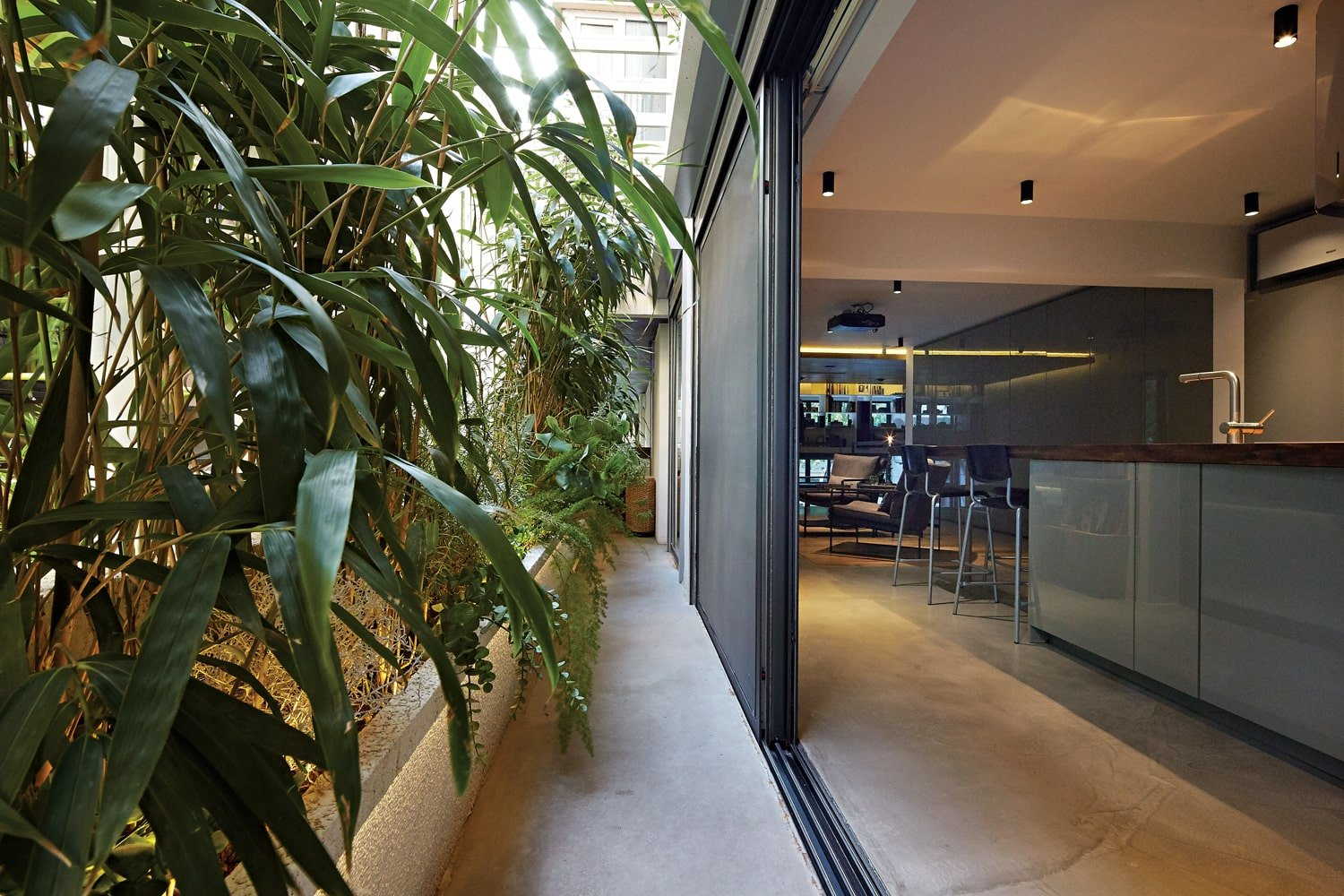 The large glass wall of the kitchen can open up to a long and narrow outdoor area with a miniature garden dominating the wall.