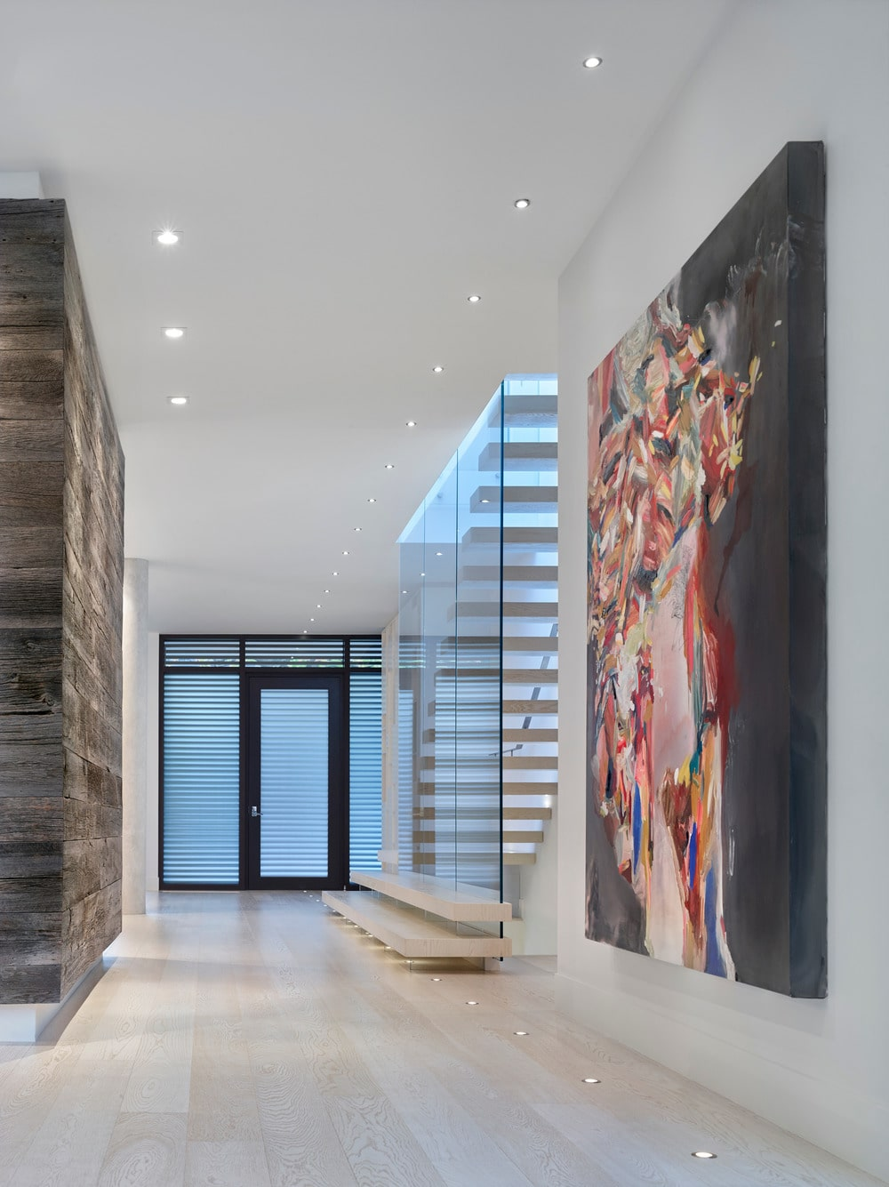 This is a simple and spacious foyer with a glass main door that has black frames to stand out against the bright white walls and ceiling that has recessed lights.