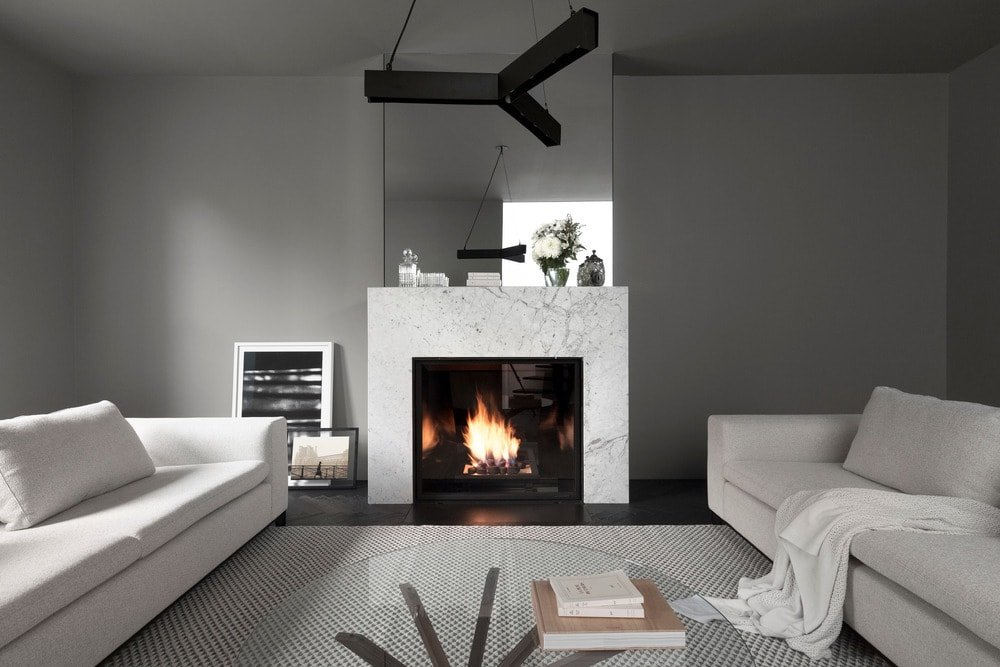 The living room has a couple of white sofas flanking a glass-top coffee table across from the fireplace with a white mantle.