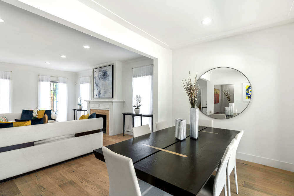 This simple and charming dining room has a black rectangular dining table surrounded by white modern chairs to match the white walls and ceiling.