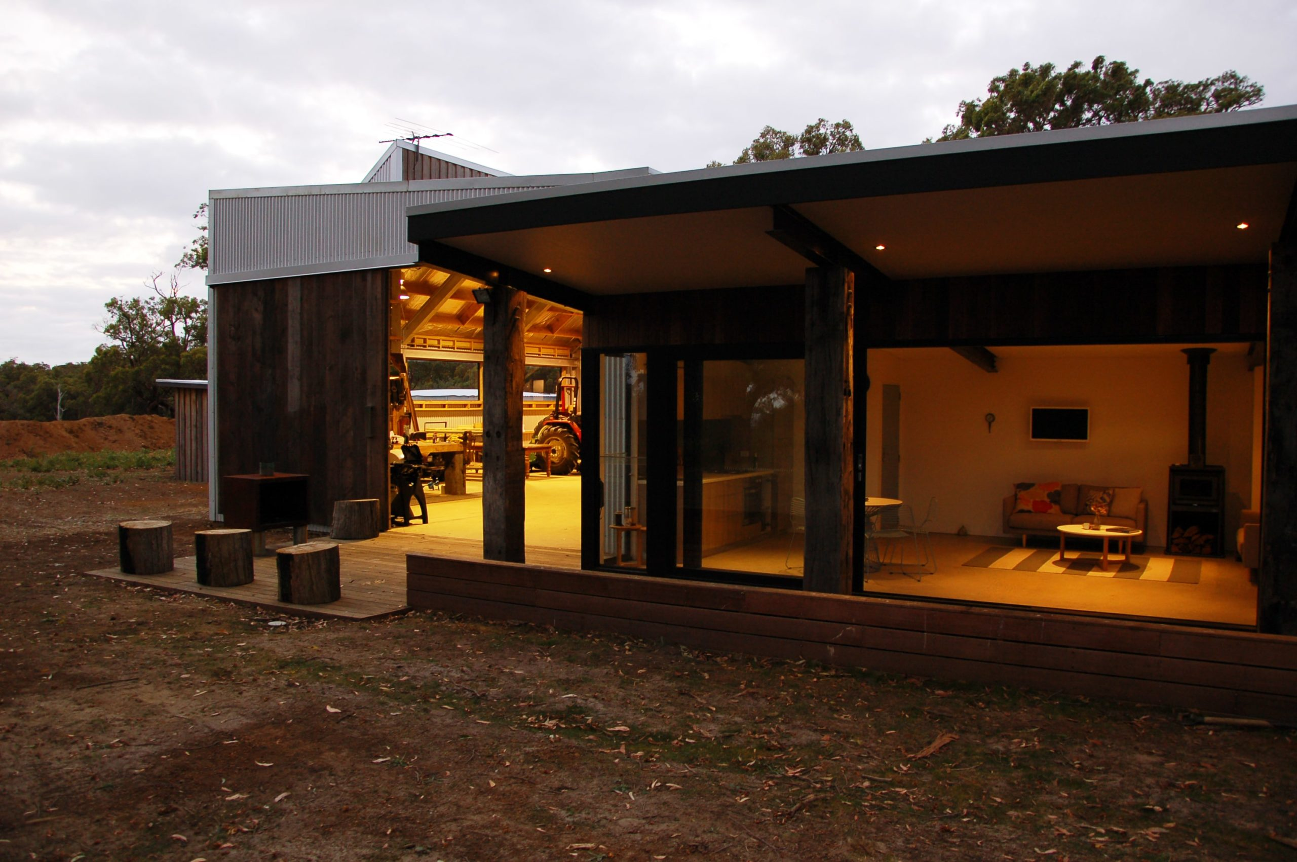 This view from the back of the house reveals the great room inside with a living room and kitchen. On the left side, there is a rustic sitting area with tree stumps just outside the large door of the shed and garage.
