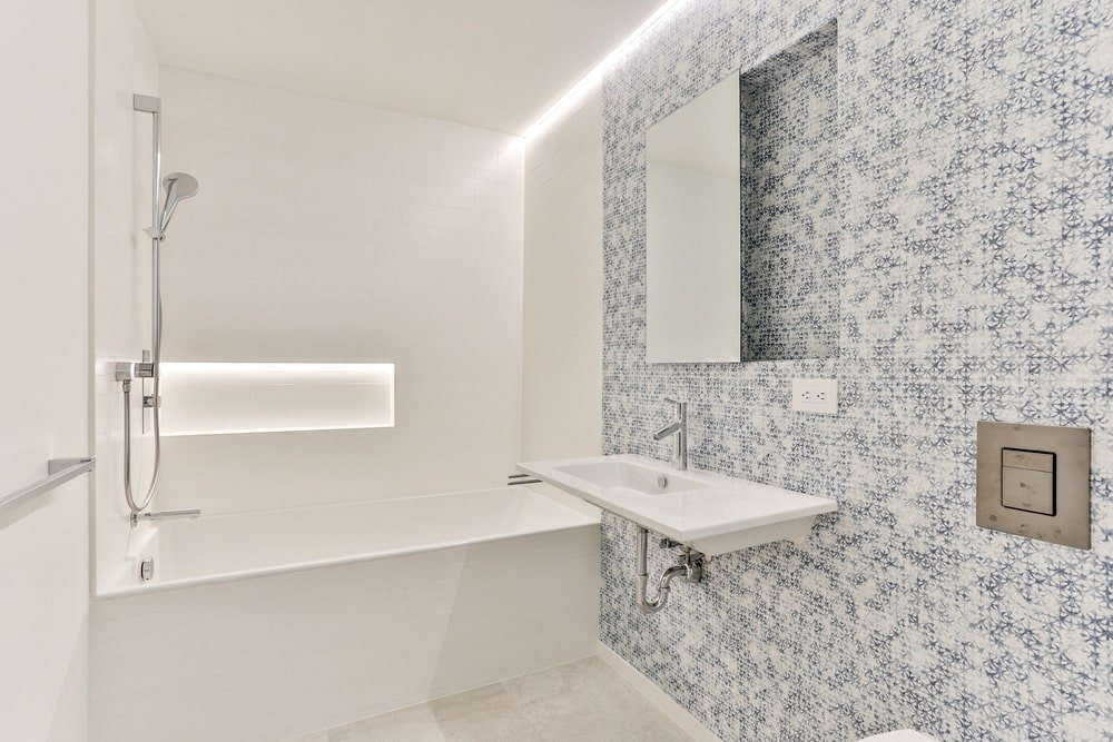 This bathroom has a patterned gray and white wall with the floating sink. This matches well with the beige bathtub on the far side that blends well with its beige walls and flooring.