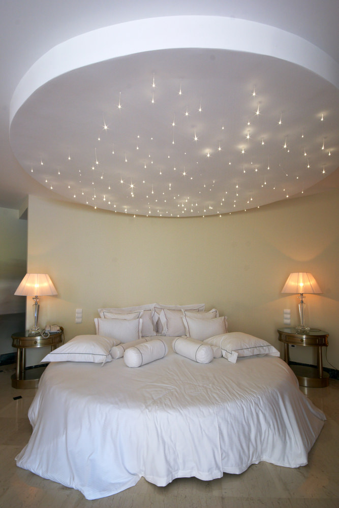 Bedroom with star lights on round ceiling with round bed