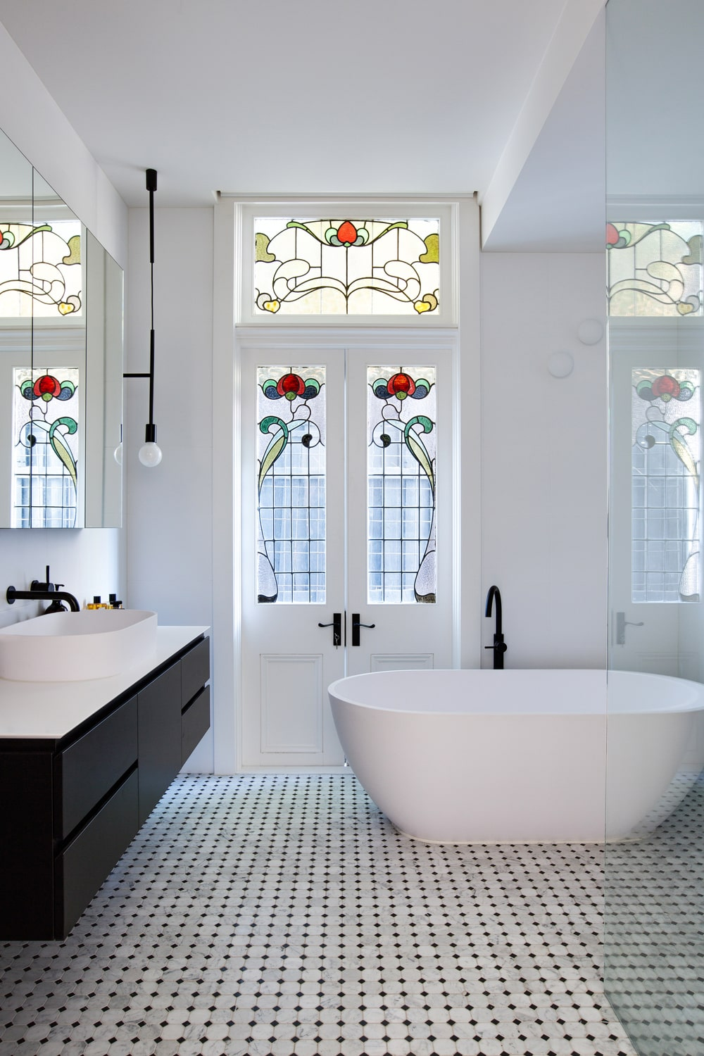 This bathroom has a black floating vanity contrasted by its white countertop and the white walls. Next to it is the freestanding white bathtub by a lovely set of doors with stained glass.