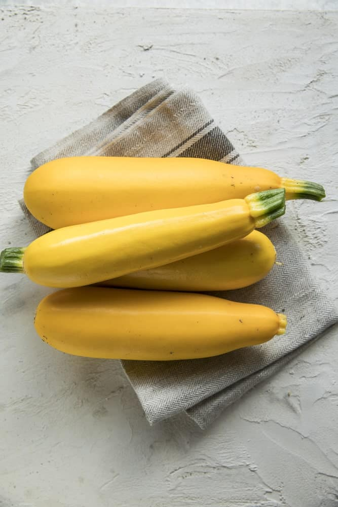 Four pieces of crookneck squash with a bright yellow tone.