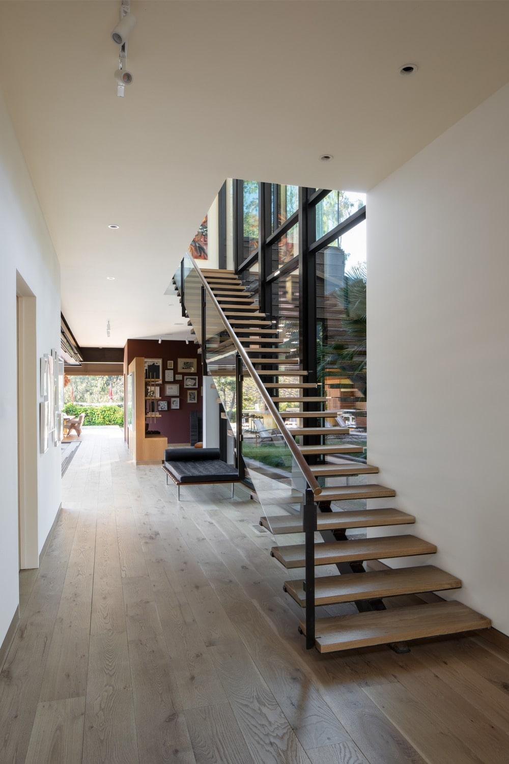 This is the simple foyer with a modern staircase bordered with glass. It has light wooden steps that match well with the hardwood flooring.